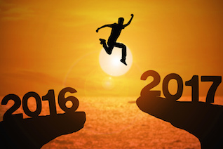 Silhouette of young man jumping between 2016 and 2017 years with beautiful sunset at the sea.